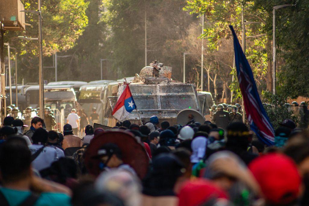 Camiones hidrantes y carabineros pretenden avanzar para disolver la manifestación, pero centenares de personas le cierran el paso. En Santiago de Chile. El 16 de noviembre de 2019.